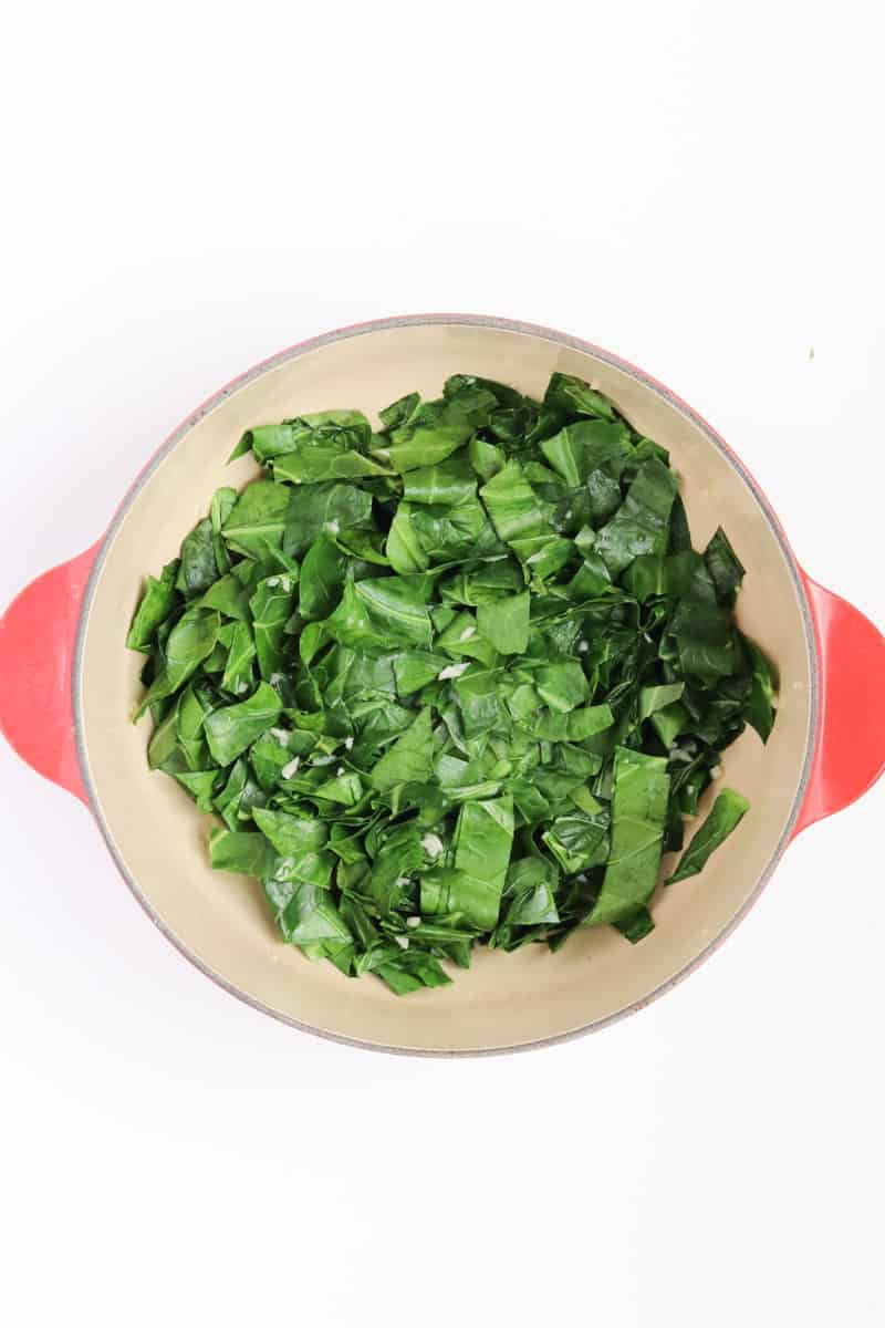 bright green collard greens and garlic in a red dutch oven.