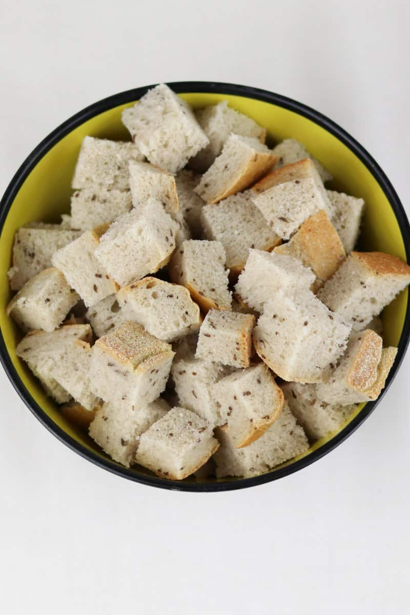 light rye bread cubes in a yellow bowl with a black rim.