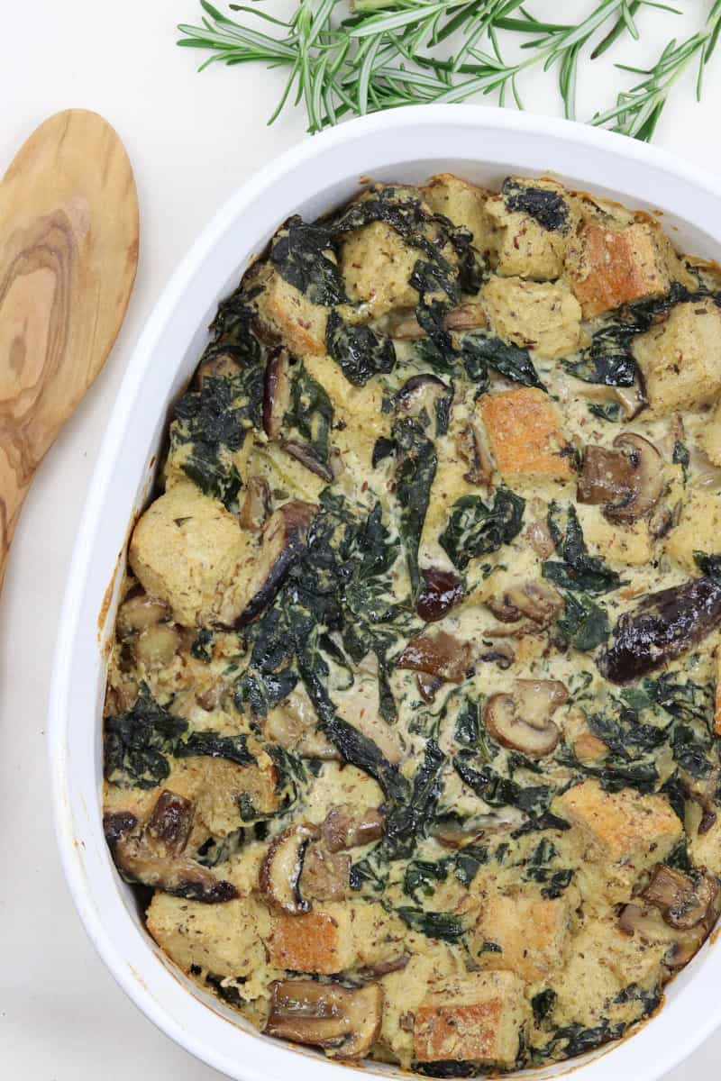 Kale Mushroom Bread Pudding in a white baking dish with wooden spoon and rosemary