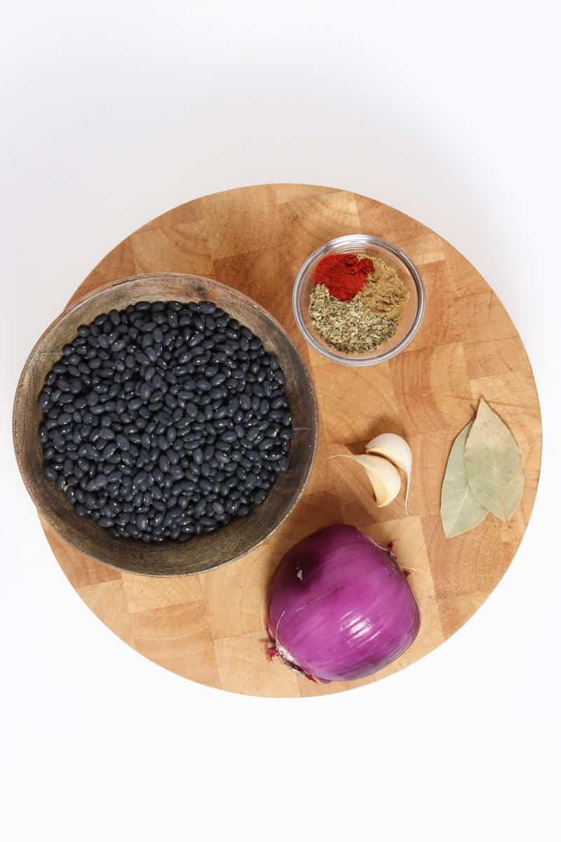 dried black beans, red onion, smoked paprika, oregano, garlic and bay leaf on a round cutting board.