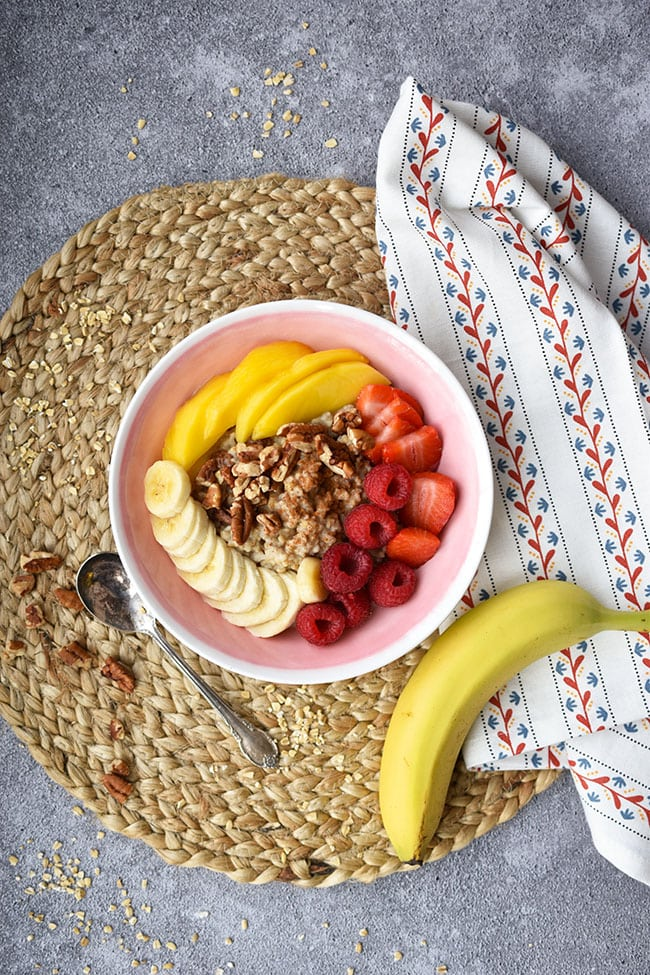 Maple pecan oatmeal topping strawberry smoothie bowl with bananas, mango and strawberries.