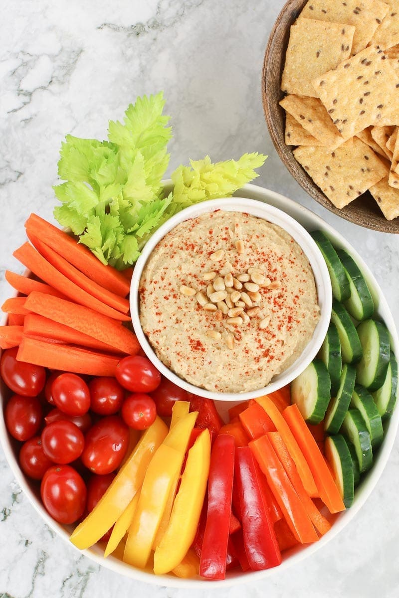 classic hummus veggie platter with carrots, cucumbers, cherry tomatoes, bell peppers celery and crackers