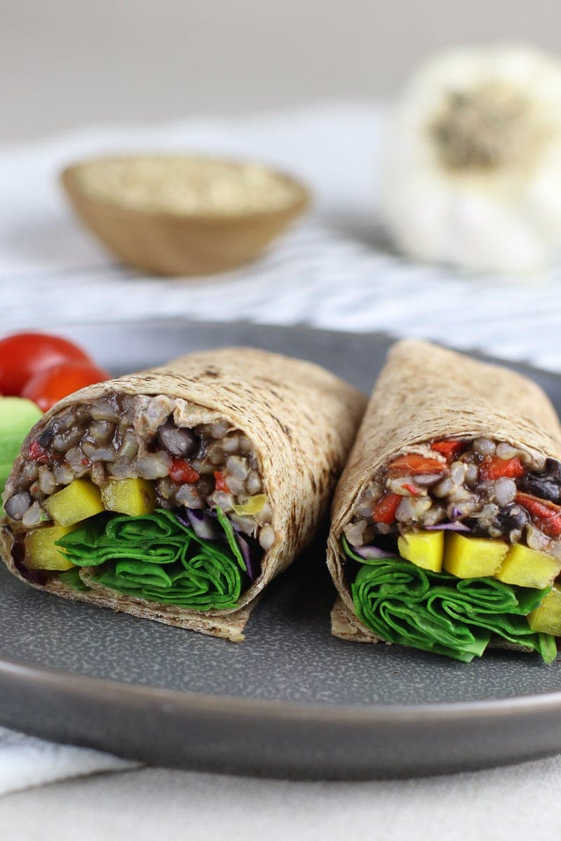 Smoky Black Beans & Rice Wrap with yellow peppers and spinach sandwich on a gray plate