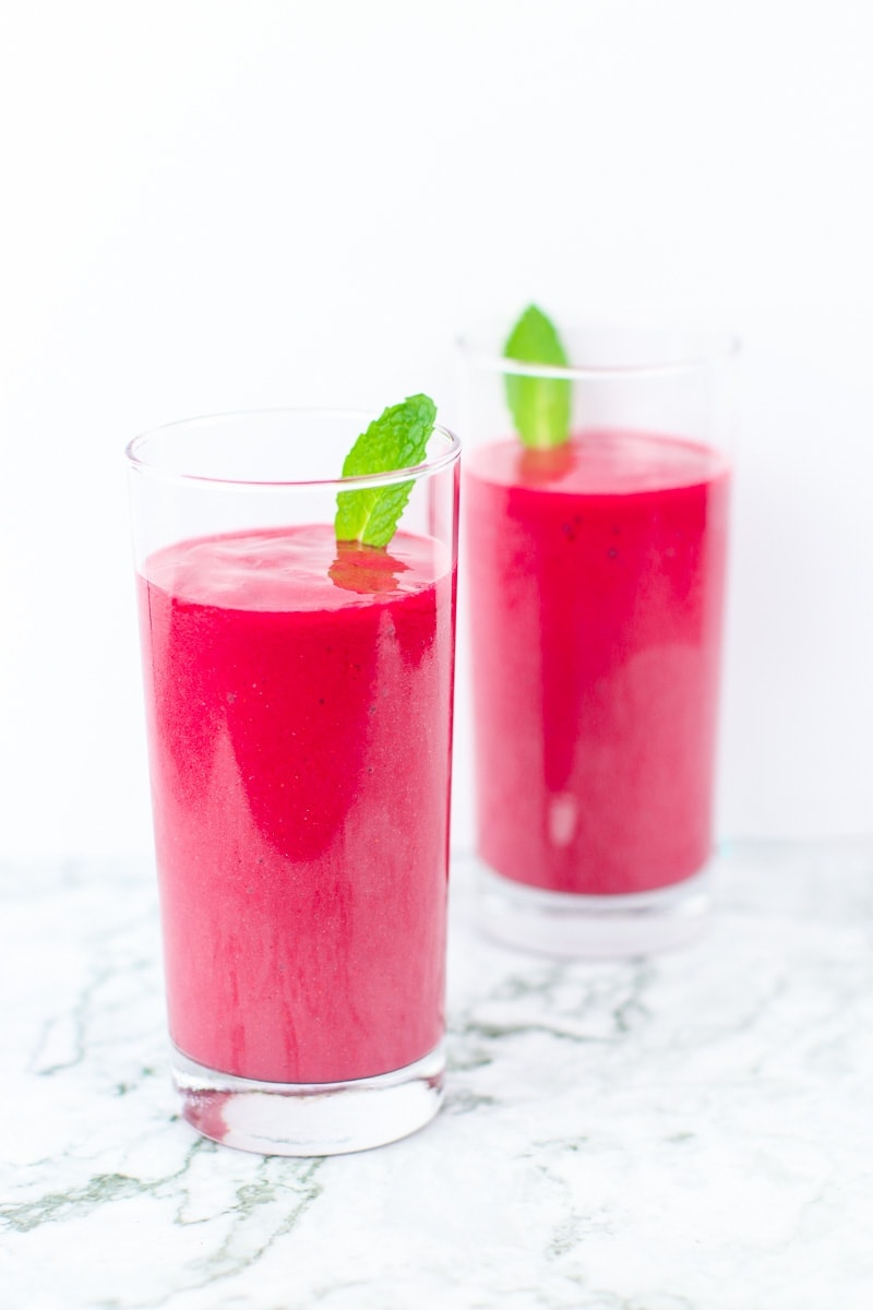 2 tall glasses of hibiscus tea pink smoothies with mint garnish