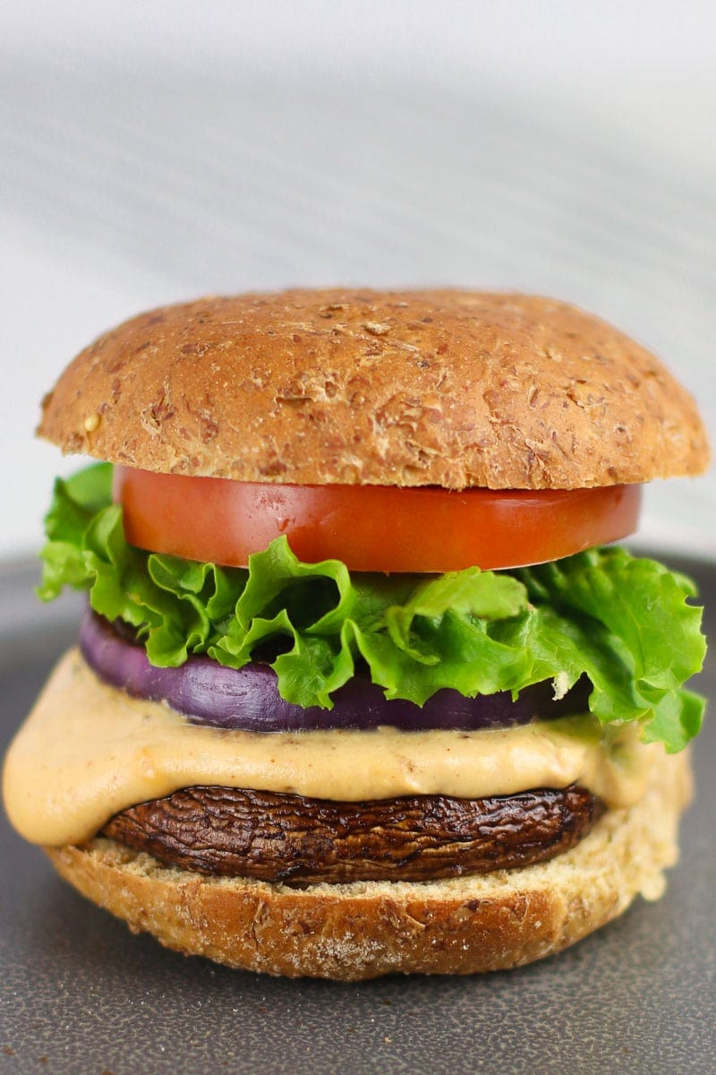 Close up of vegan portobello mushroom burger with cheddar sauce lettuce tomato and red onion