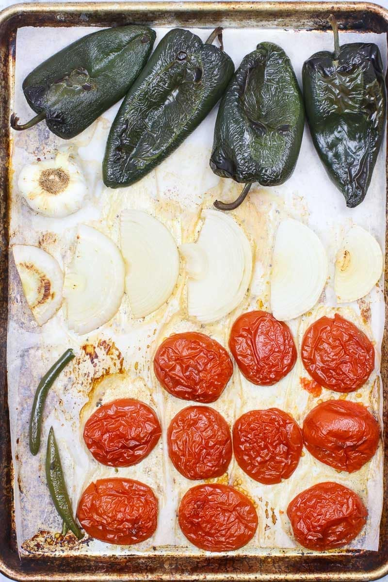 poblano peppers, onions, garlic, tomatoes and Serrano peppers on a sheet pan