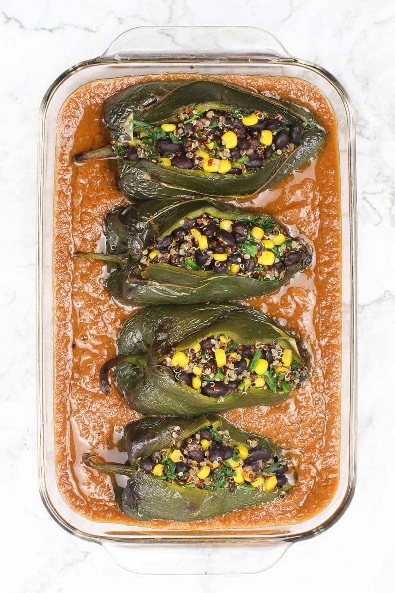 vegan chile relleno in red sauce in a clear baking dish