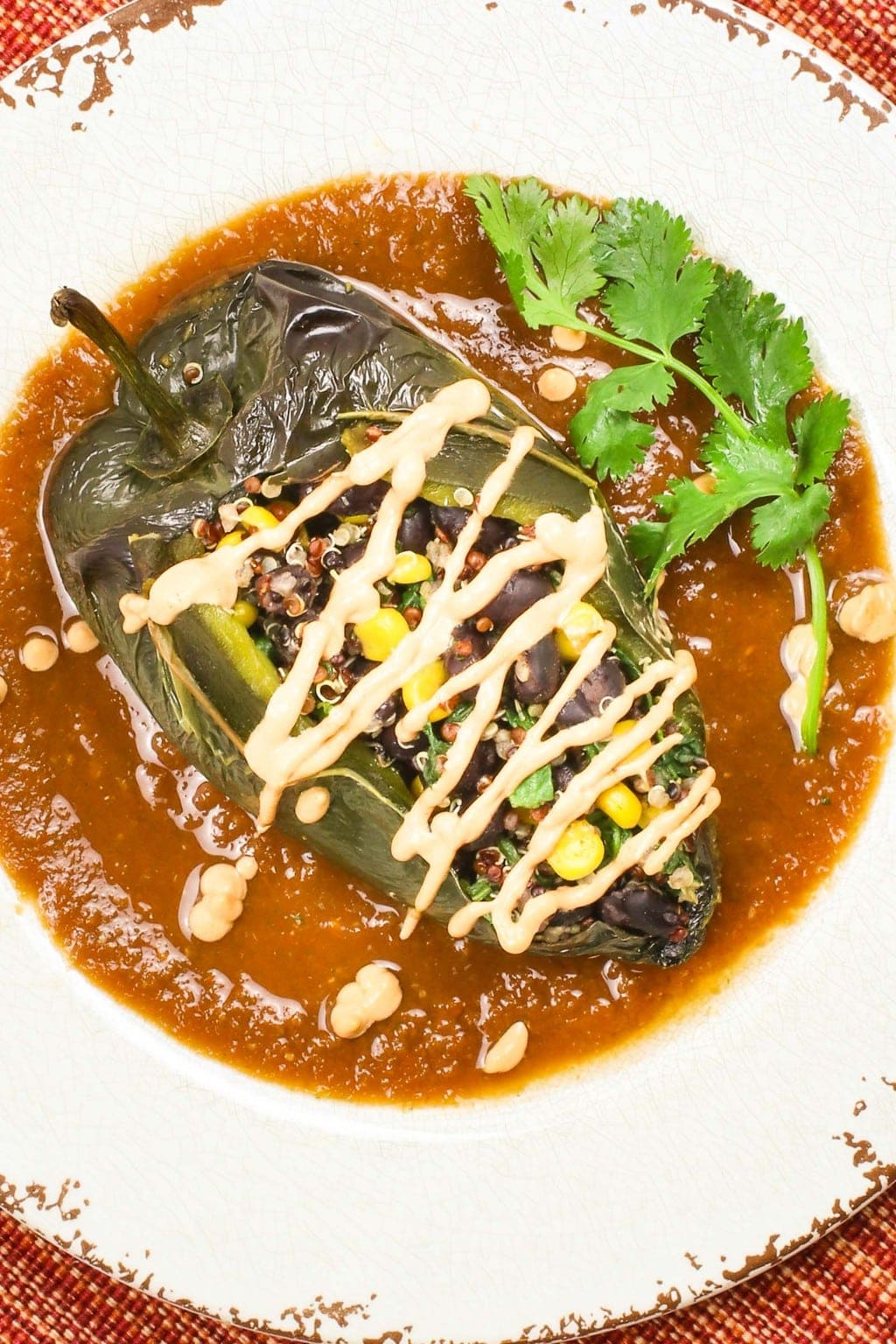 vegan chile relleno on with red sauce and vegan cheese sauce, on a red and orange placemat