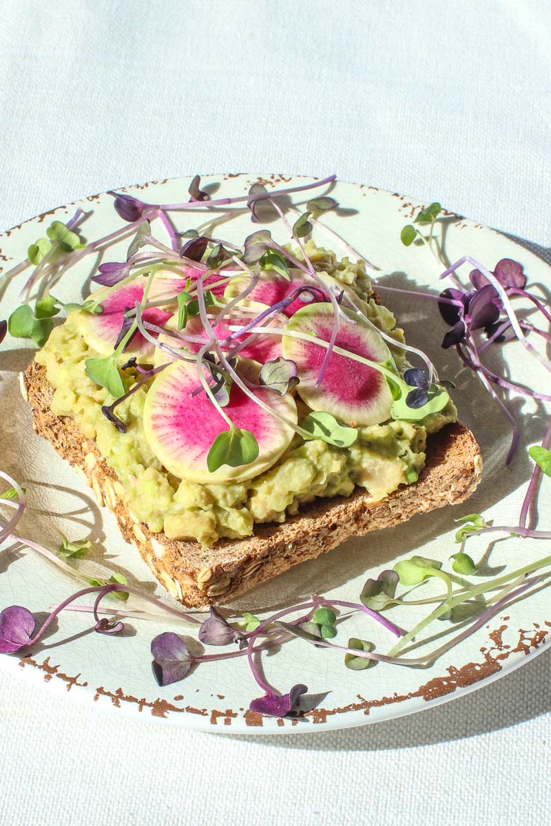 vegan egg salad on toast with beauty heart radishes and micro greens on a plate