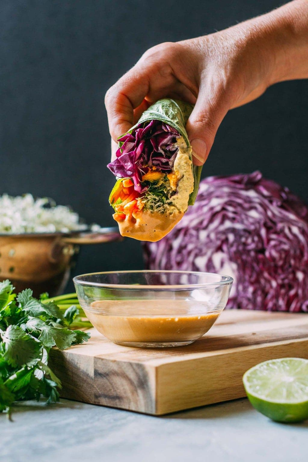 Hand dipping a Mango cashew collard wrap into peanut sauce on a cutting board