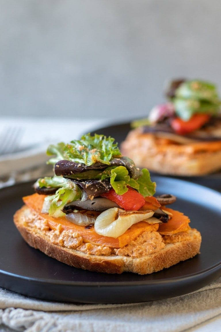 roasted vegetable sandwich with smoky walnut sauce on a black plate
