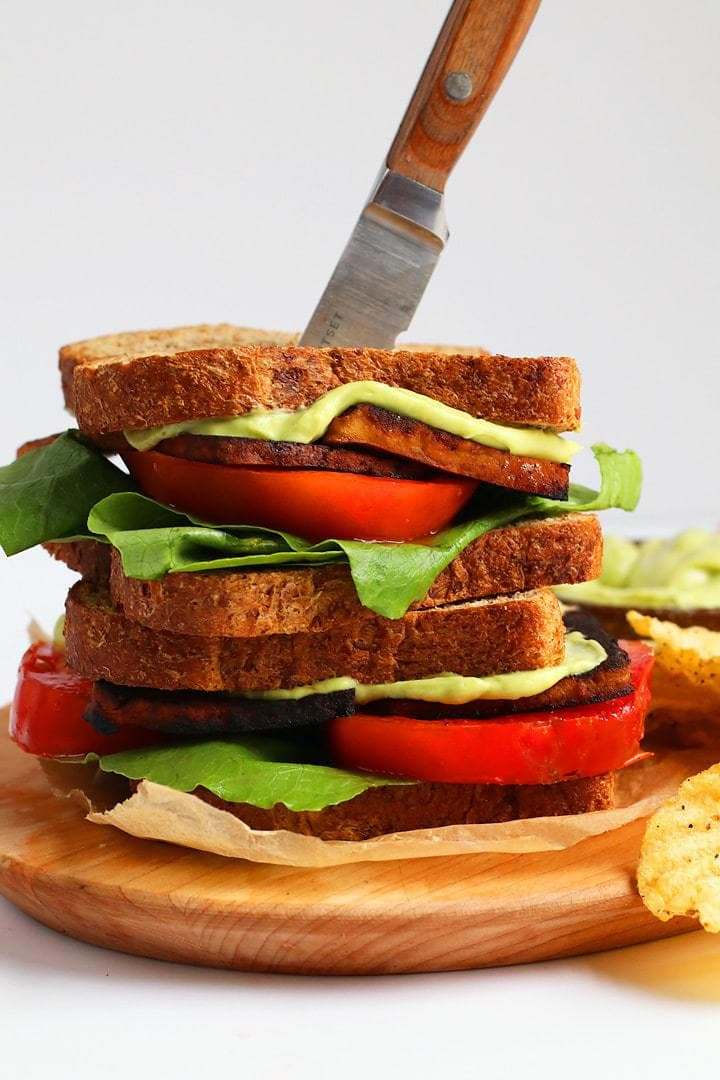 Vegan BLT Sandwich with Avocado Mayo on a cutting board with a knife inserted into the top
