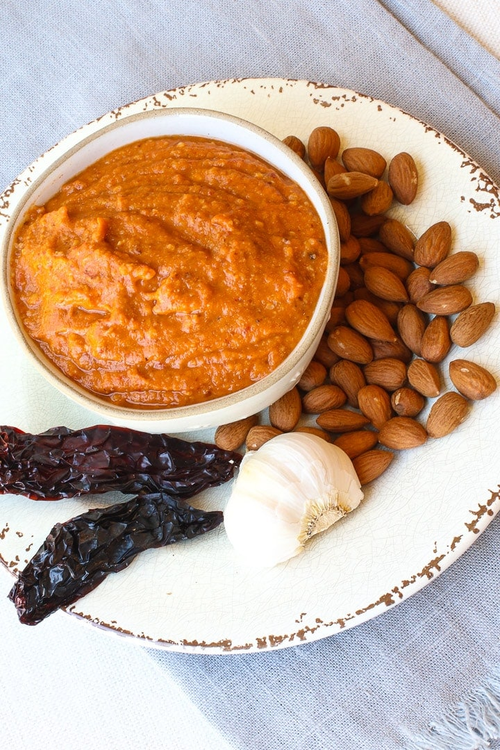 Romesco Sauce in a bowl on a white plate and blue towel with chilis, almonds and dried peppers