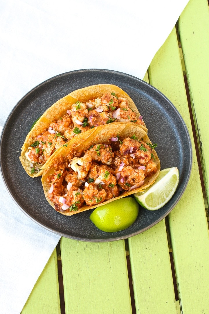 Cauliflower Tacos with Romesco Sauce on a dark gray plate with limes on a lime green table
