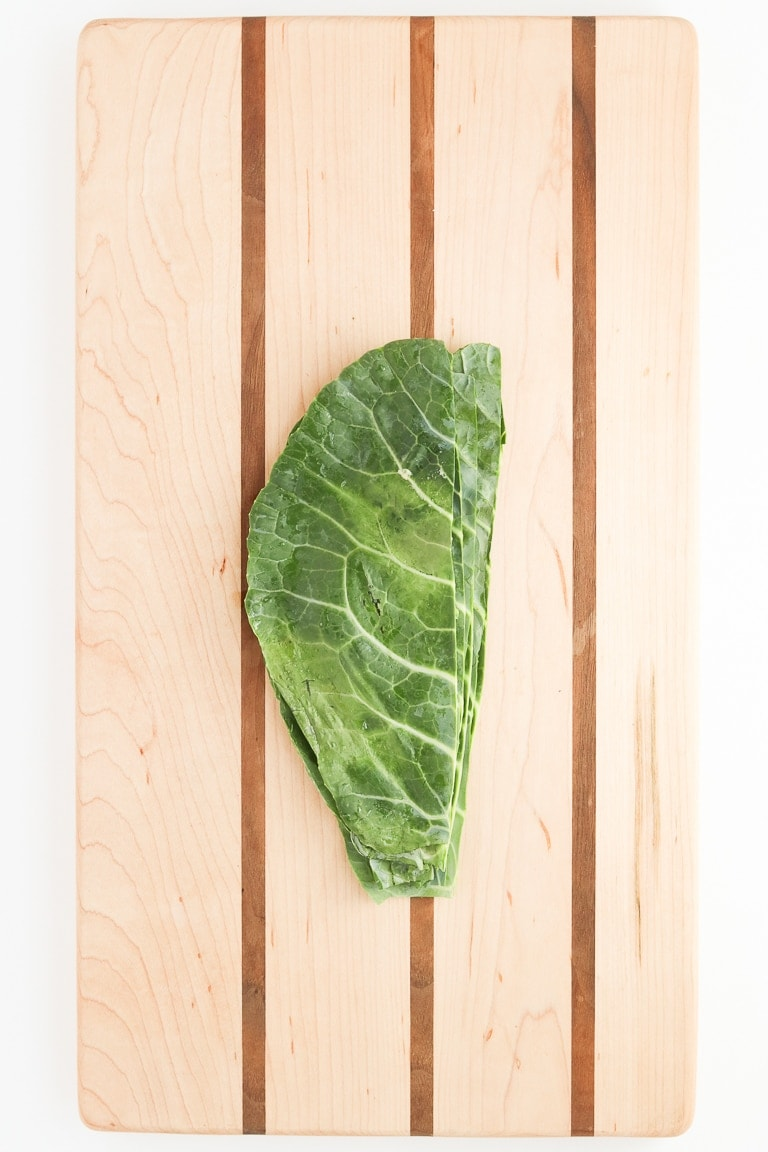 collard green leaf halves piled on top of each other on a cutting board.