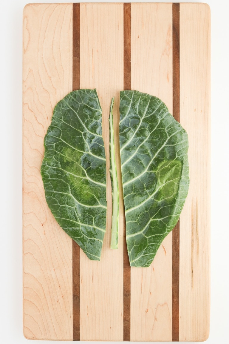 collard green leaf with center stem cut out on a cutting board