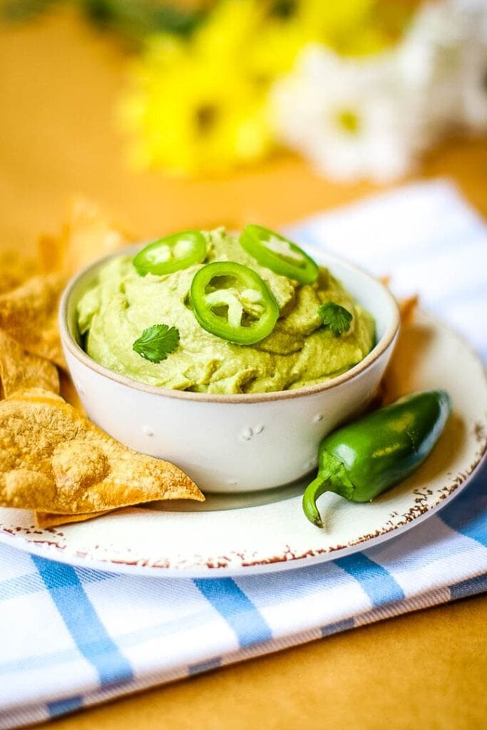 Spicy oil free hummus on white plate with tortilla chips and jalapeño