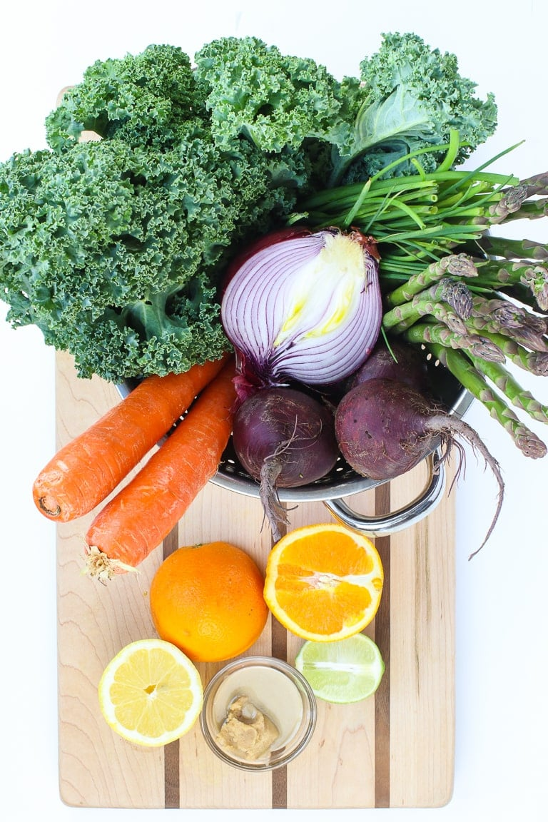warm kale salad ingredients on a cutting board, kale, red onion, carrots, beets, lemon, lime, orange, miso, tahini