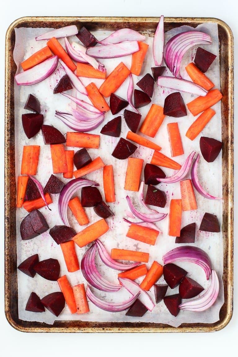 Baking sheet with parchment paper and carrots, beets and red onion