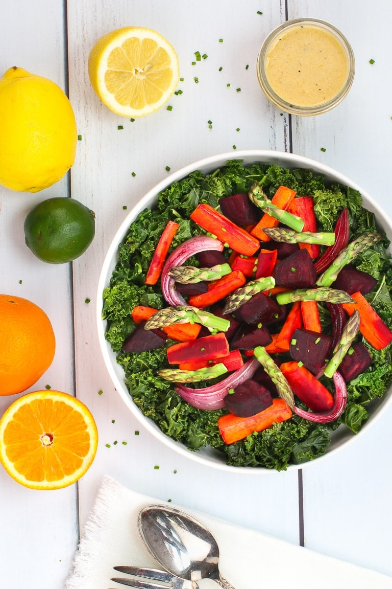 Warm kale salad with roasted carrots, beets and asparagus and citrus dressing on a white table with lemons, oranges and lime