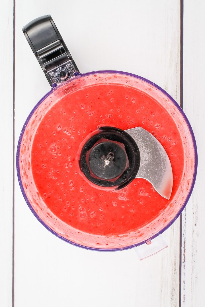 strawberry vinaigrette in a food processor on a white plank background.