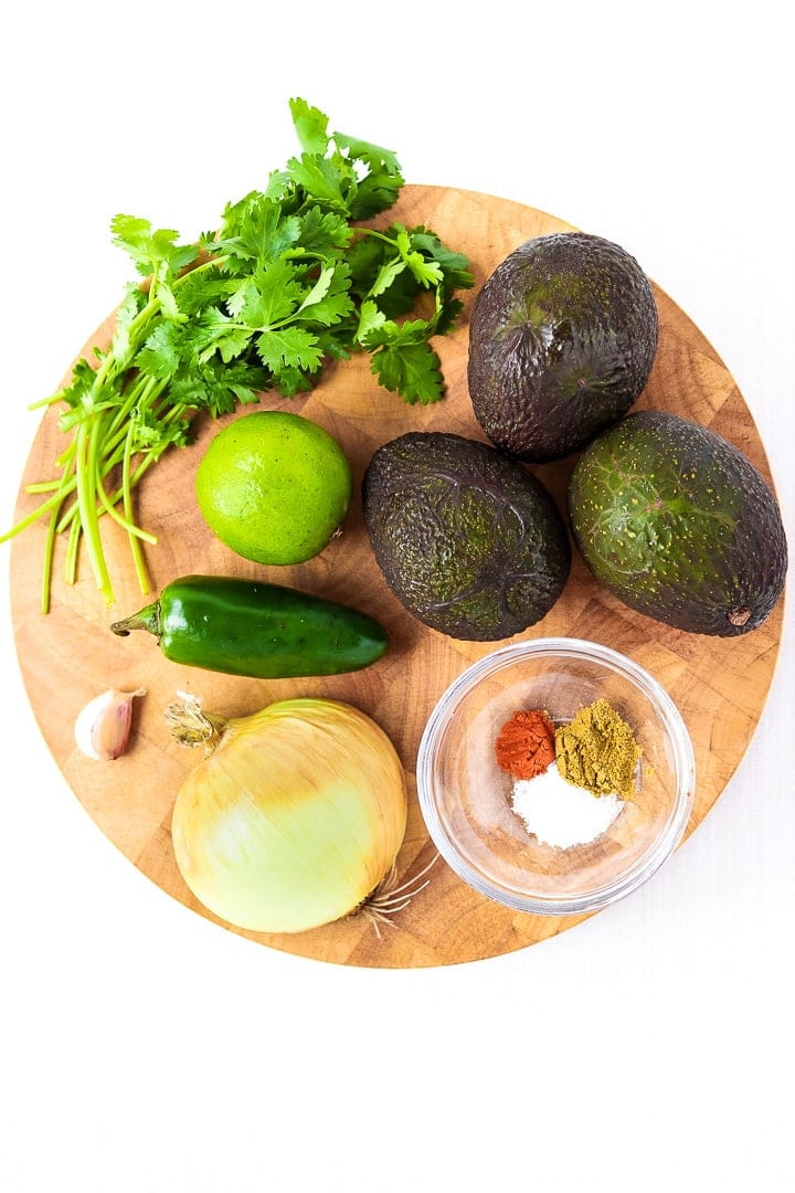 Round Cutting board with avocados, cilantro, jalapeño, lime, garlic, onion and spices.