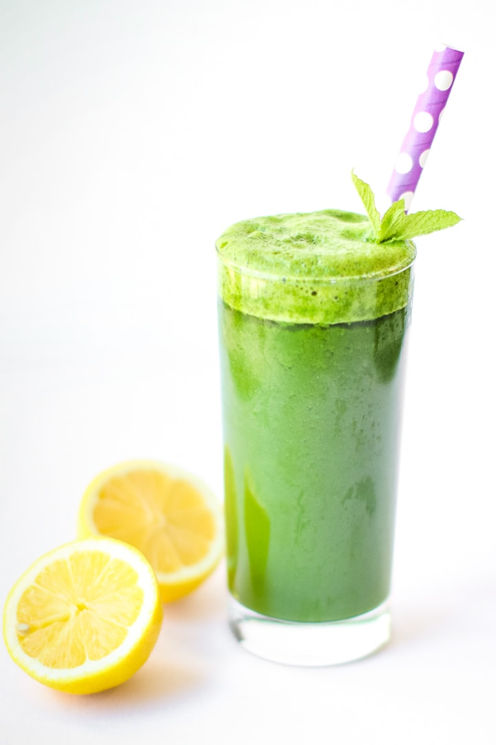 Green smoothie with ginger, in a tall class with cut lemons, mint garnish, and purple polka dot straw