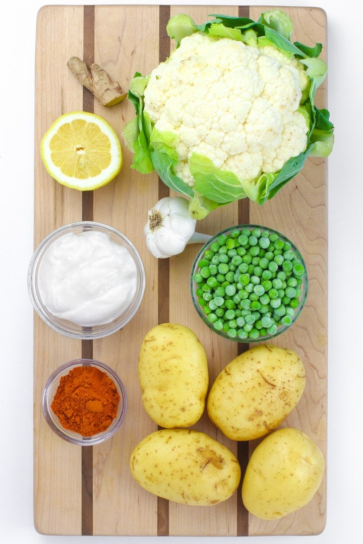 cutting board with cauliflower, lemon, ginger, yogurt, tandoori spice, garlic, potatoes and peas.