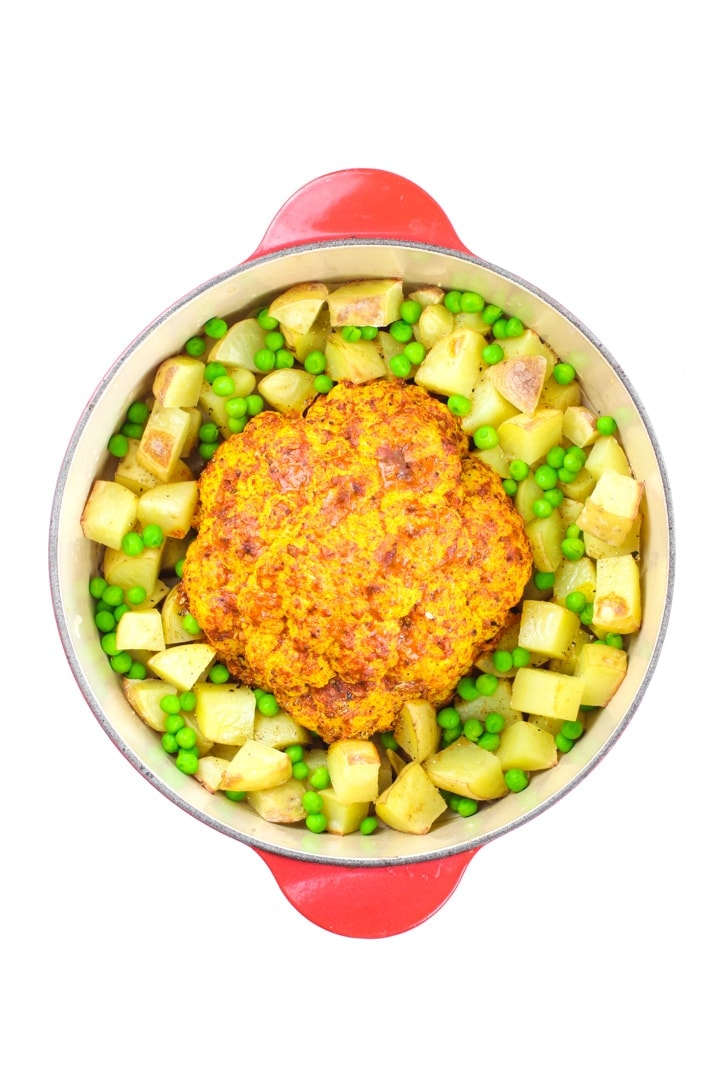 whole roasted cauliflower tandoori with potatoes and peas in a red Dutch oven.
