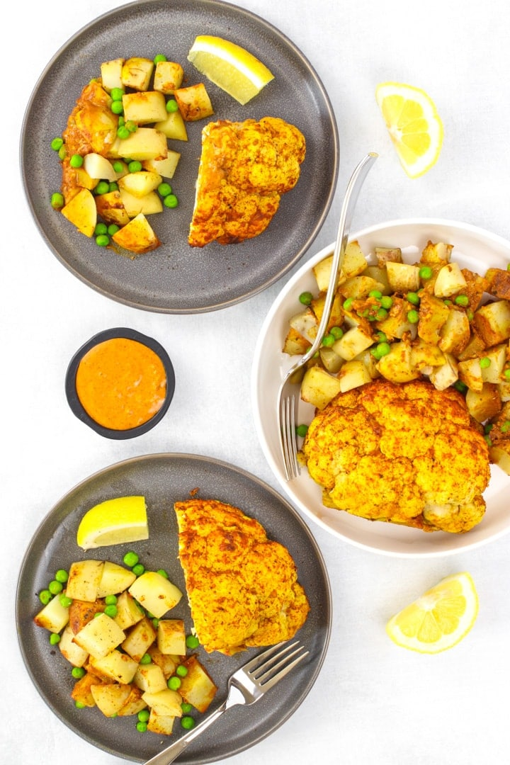 whole roasted cauliflower tandoori with potatoes, peas and lemon wedges on dark gray plates and in a white serving dish. A dish of sauce on the side.