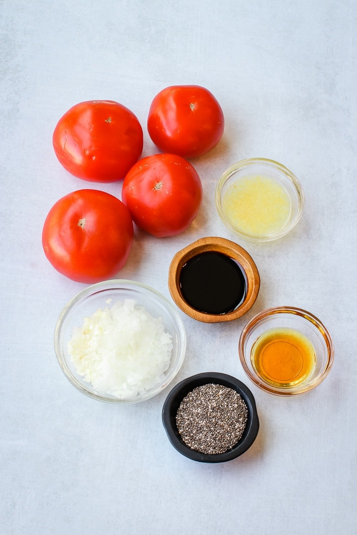 tomatoes, lemon, maple syrup, shallot, garlic, balsamic vinegar and chia seeds on a gray background.