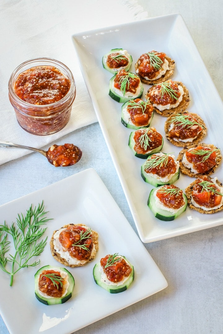 Almond ricotta cheese and tomato jam canapés on crackers and cucumber slices with dill a white platter and white plate. Jar and spoon of tomato chia jam on gray background.