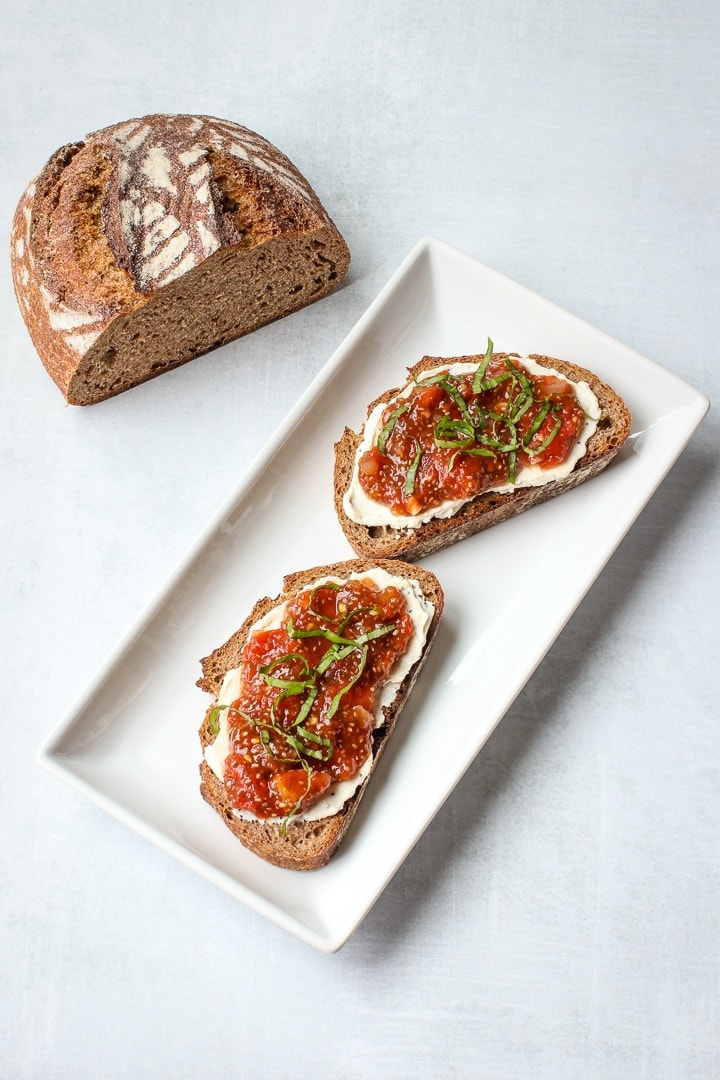 Tomato chia jam with nut cheese and basil ribbons on bread on a white platter, with a alf loaf or bread.
