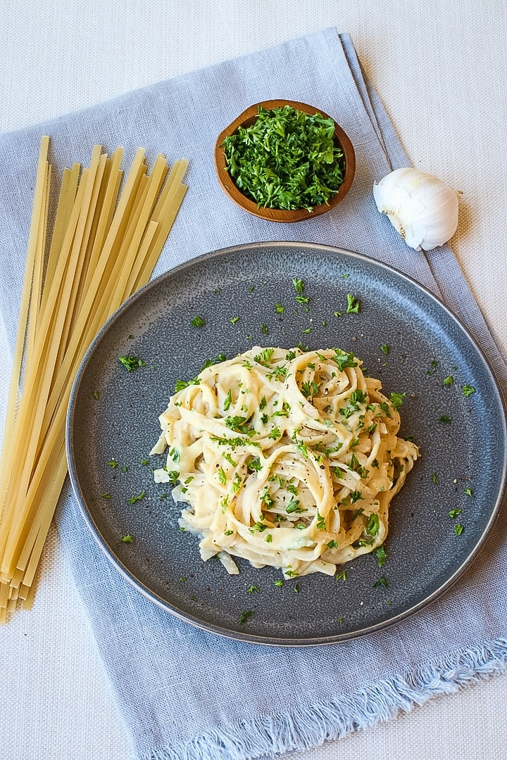 Vegan alfredo sauce pasta on a dark gray plate with dried fettucine, parsley and garlic on a blue towel