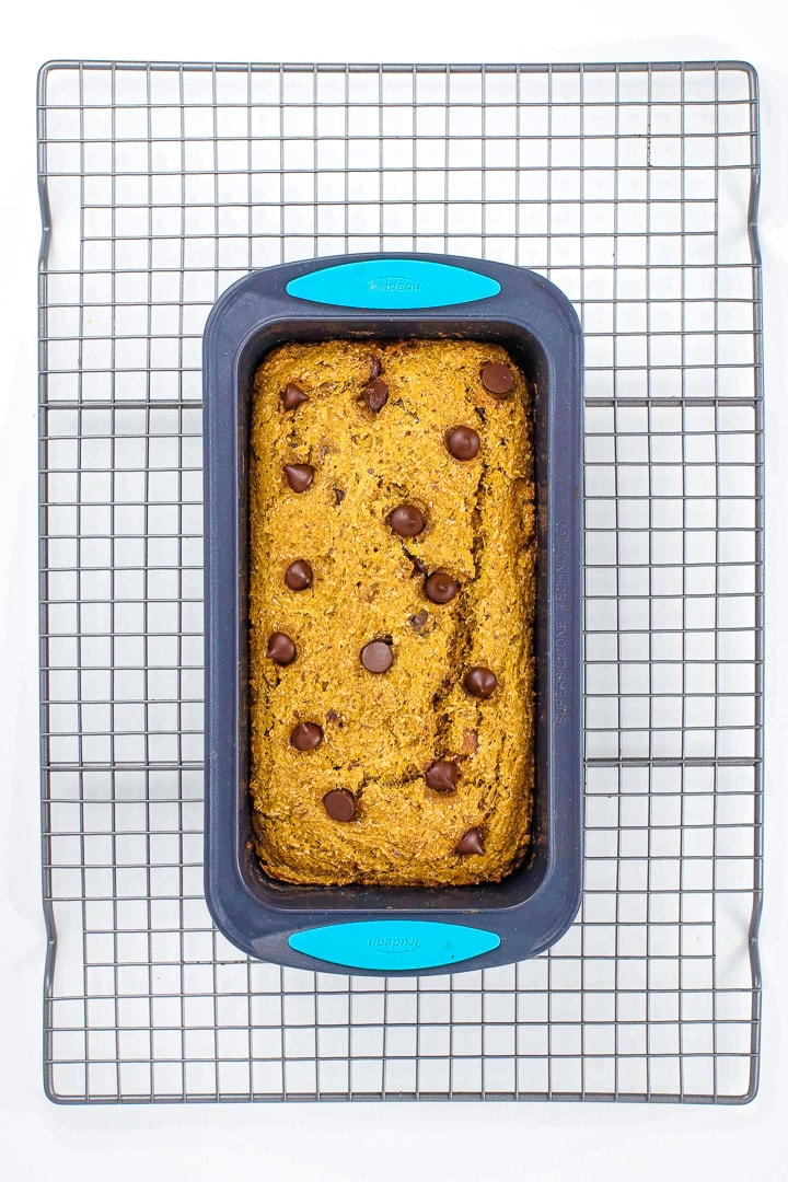 vegan pumpkin bread with chocolate chips in a silicone baking pan on a wire cooling grid