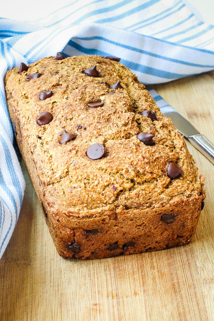 pumpkin bread with chocolate chips on a cutting board with a a pale blue striped towel and a knife