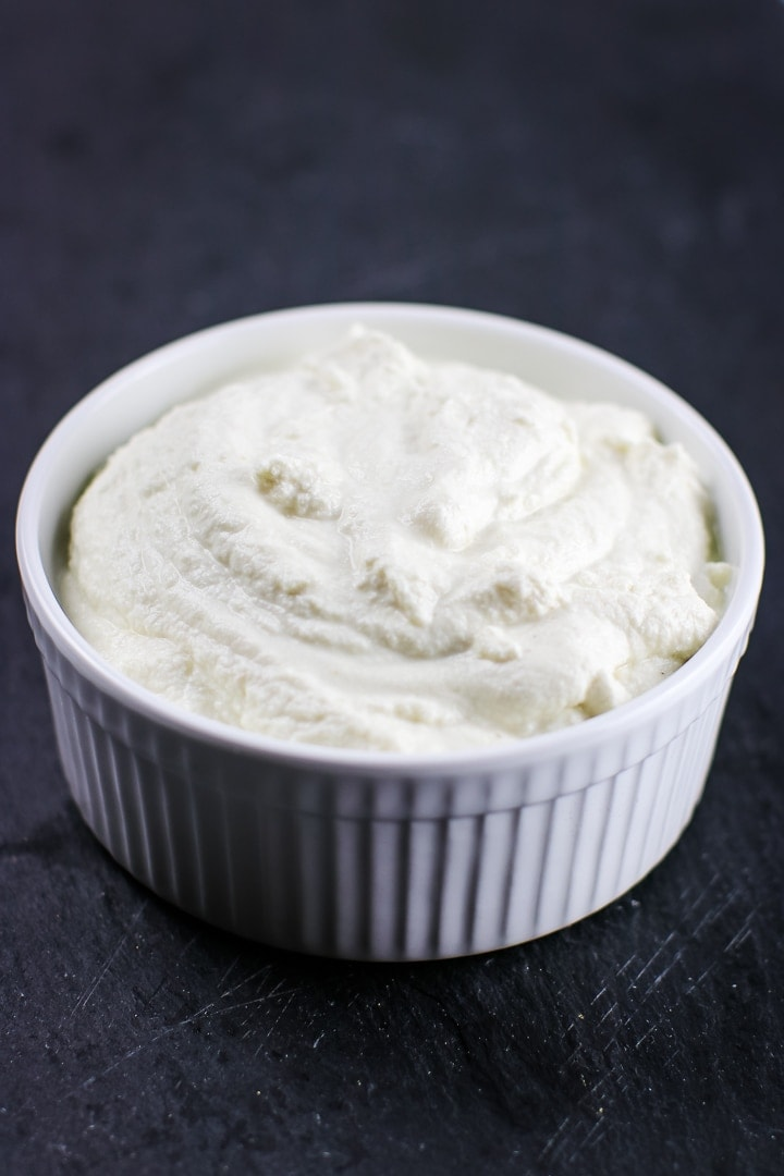 White ramekin of almond ricotta cheese on black slate.