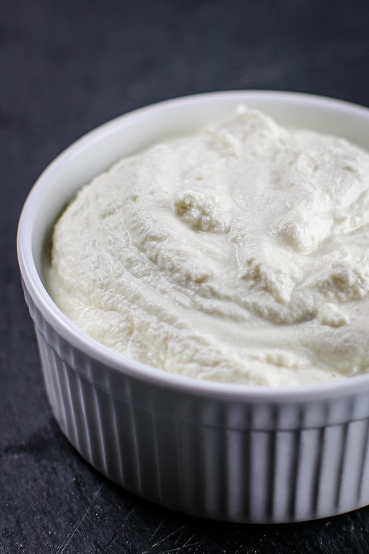 close up of White ramekin of almond ricotta on black slate.