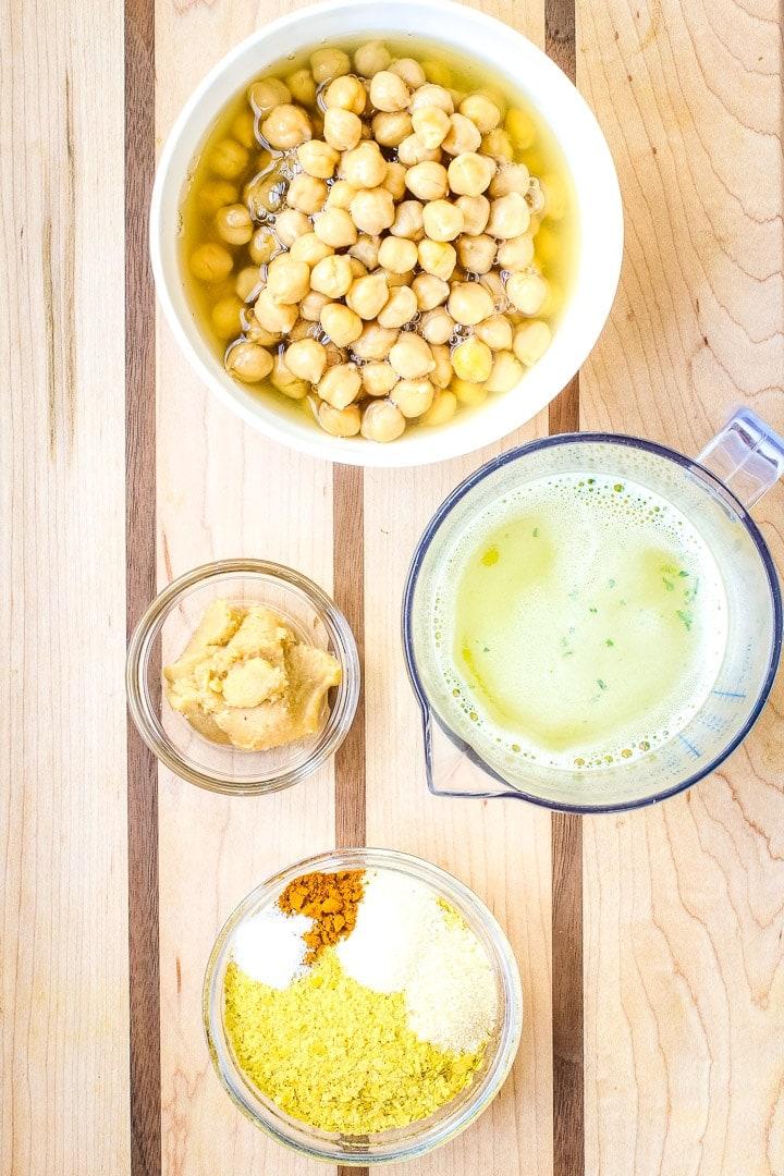 Chickpea Cheese Sauce ingredients on a cutting board: chickpeas, veggie broth, miso paste, nutritional yeast, seasonings.