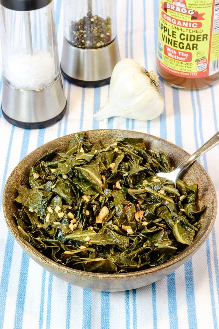 collard greens with garlic and smoked paprika in a wooden bowl on a pale blue striped towel with salt and pepper, garlic and apple cider vinegar.