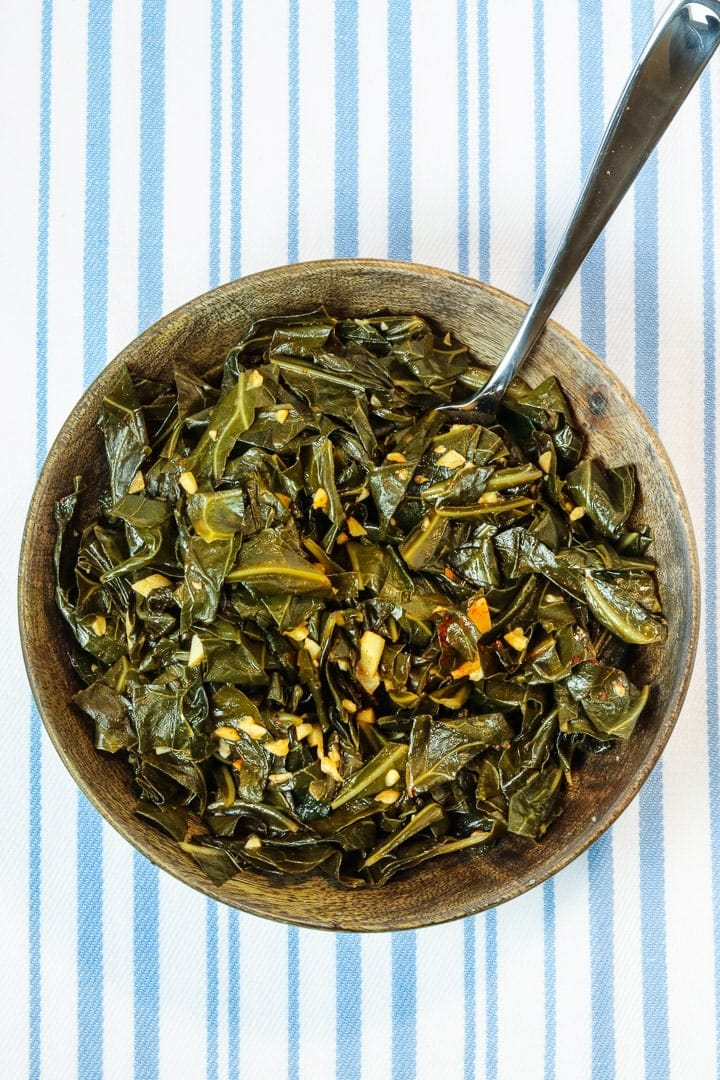 collard greens with garlic and smoked paprika in a wooden bowl with a fork on a pale blue striped towel.