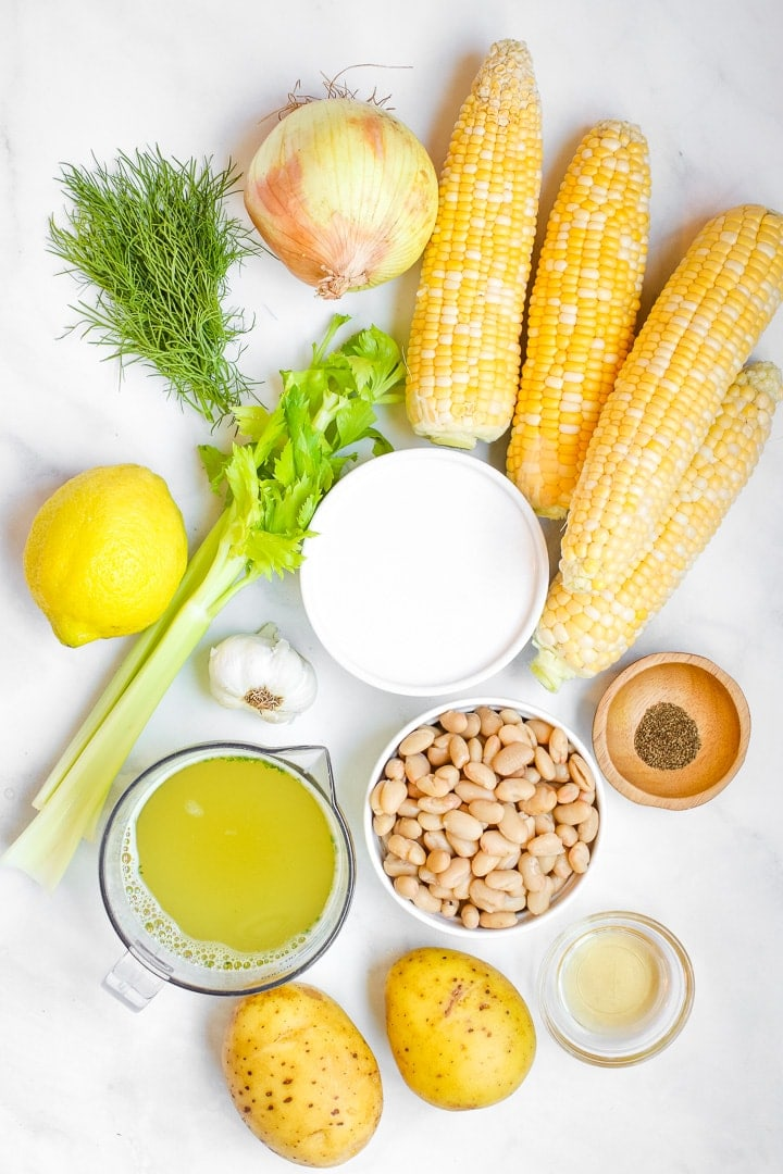 Four ears of corn, celery, dill, lemon, potatoes, broth, dish of coconut milk, cannellini beans, garlic, vinegar and celery seed on marble.