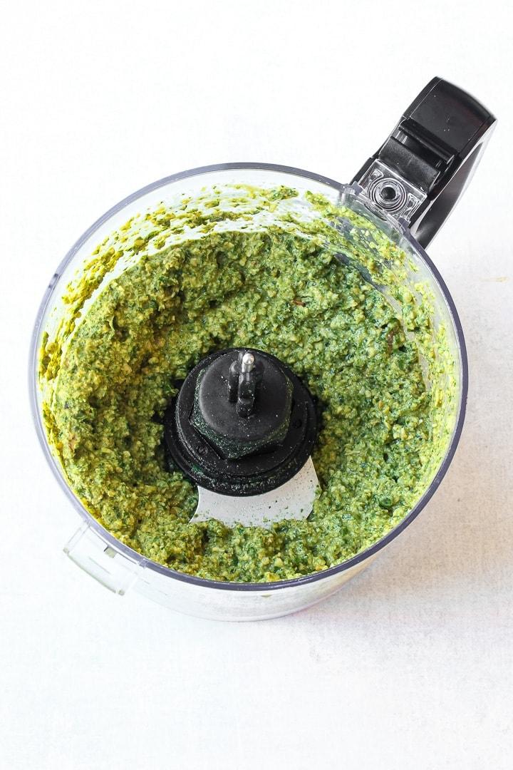 Pesto in a food processor on white.