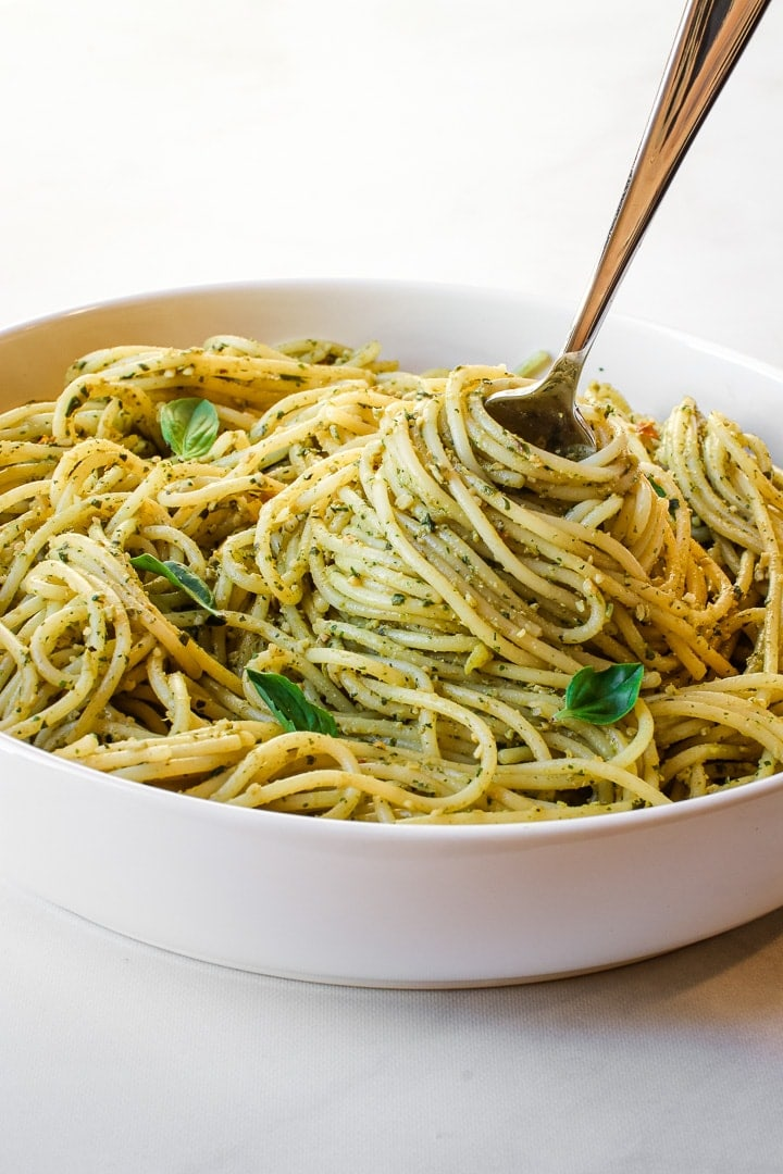 Fork twirling spaghetti with pesto sauce and basil leaves in a white bowl.