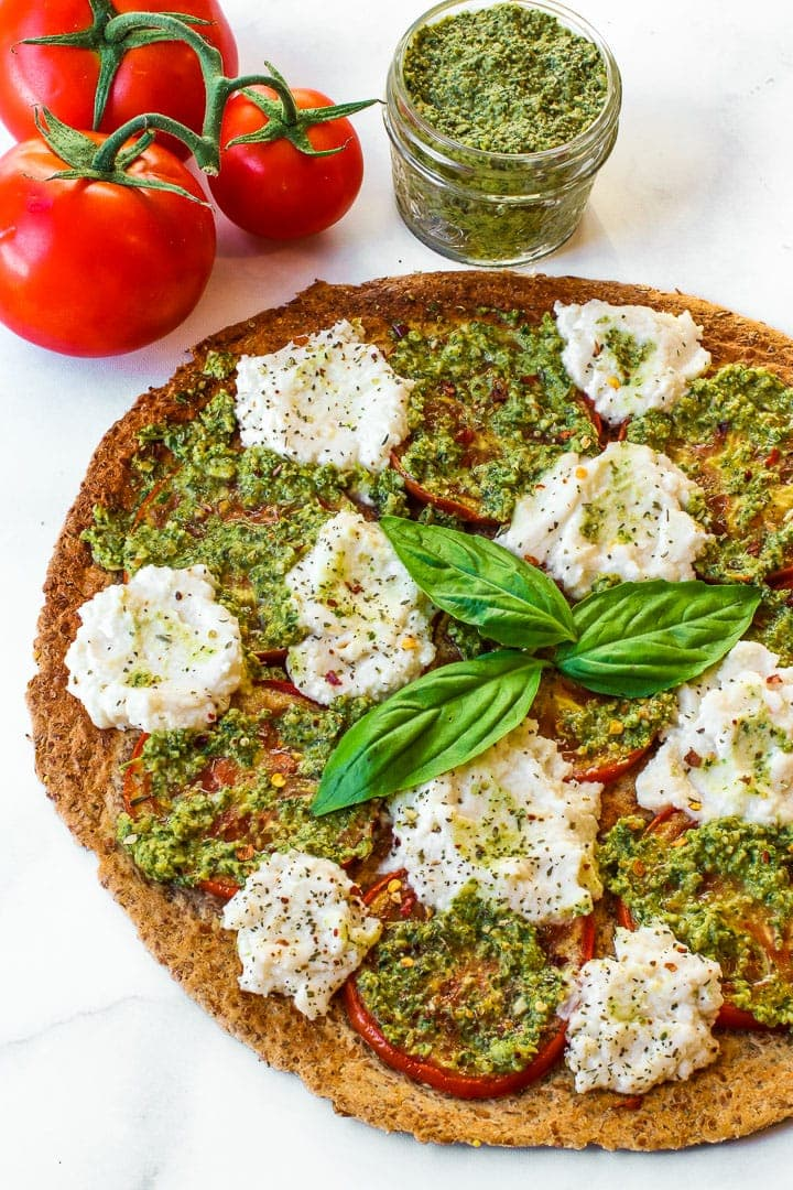 Pizza with almond ricotta cheese dollops, tomato slices, pesto and 3 basil leaves in center on marble with 3 vine tomatoes and jar of pesto.