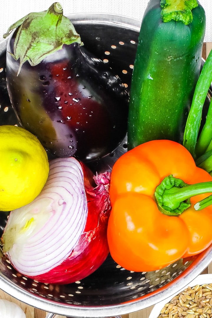 close up of eggplant, lemon, red onion half, orange bell pepper and zucchini in a stainless steel colander.