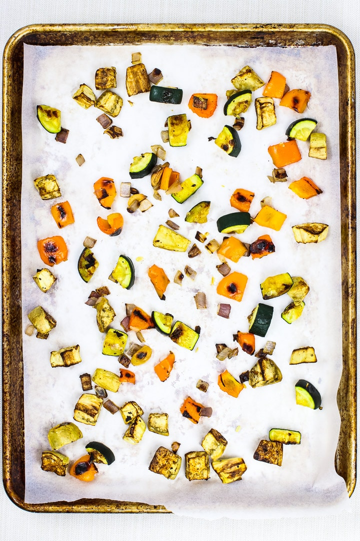 Parchment paper lined baking sheet with pieces of roasted eggplant, zucchini, orange bell pepper, red onion.