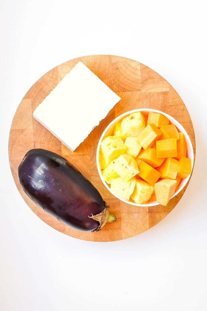 Round cutting board with tofu, eggplant and white bowl of cut squash and pinapple