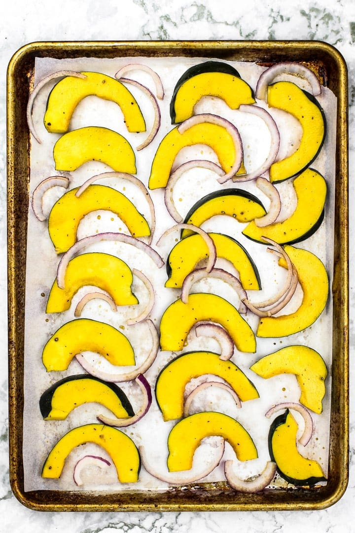 Acorn squash and red onion slices on parchment paper lined baking sheet on marble.