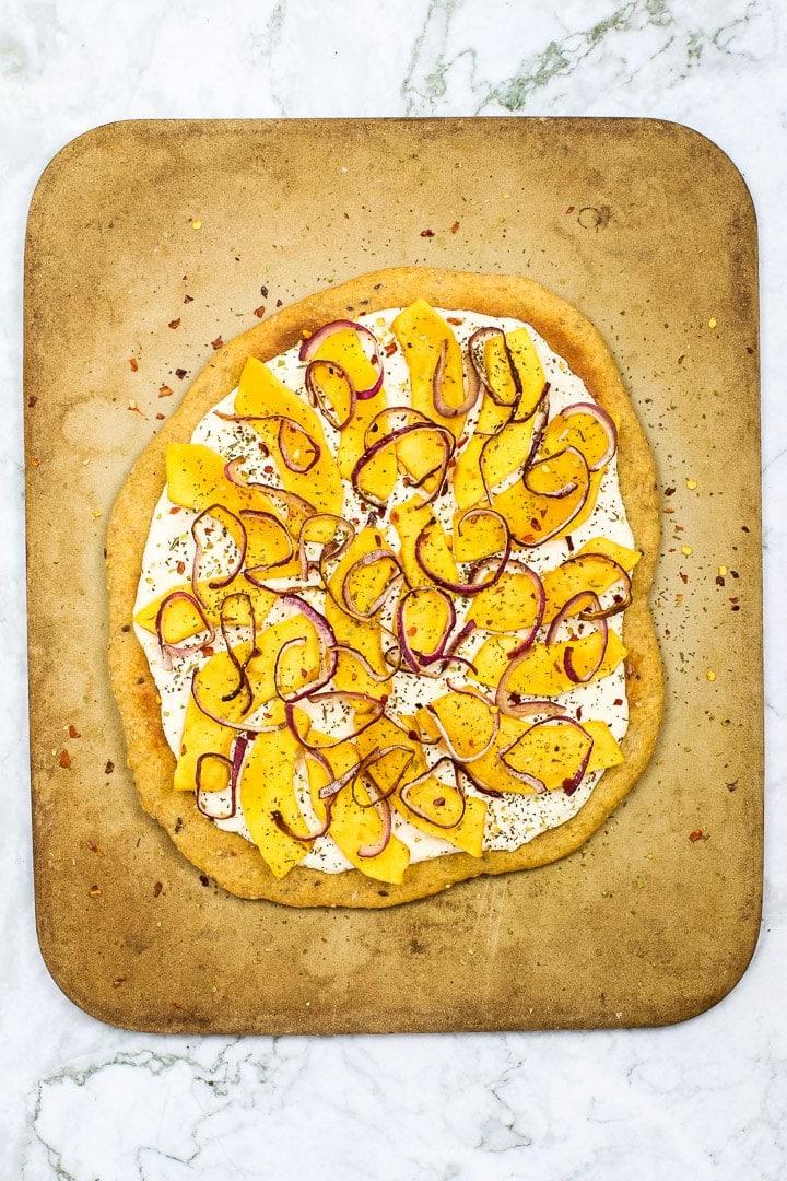Roasted squash white pizza on pizza stone on white marble.